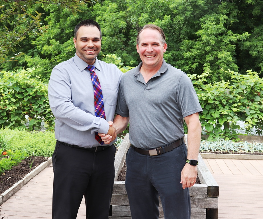 Two men shaking hands in a garden